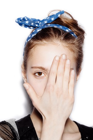 happy teenagers: Stylish cute teen girl covered her face with her hand on white background not isolated