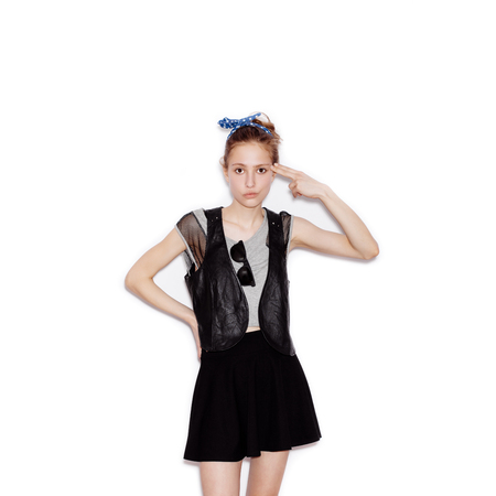 swag: Fashion swag young woman wearing black leather jacket and skirt and showing shoot of gun . Girl having fun. White background, not isolated