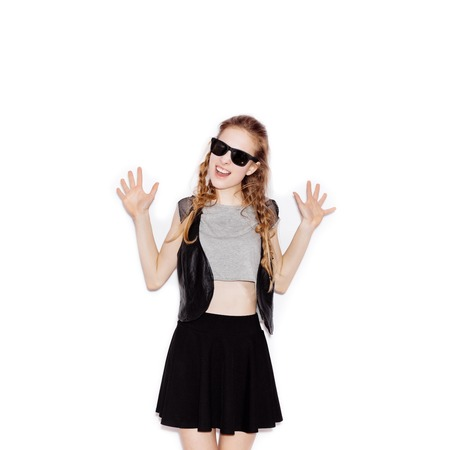 portrait studio: Cute happy girl in sunglasses with hands up laughing and joying. Young woman having fun. Not isolated on white background Stock Photo