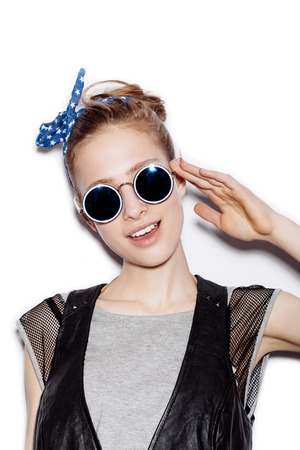 casual fashion: Fashion portrait of beautiful girl wearing sunglasses. Close-up of cute woman smiling and saluting on white background not isolated