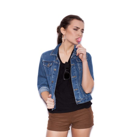 sexy young woman: Cute Girl wearing blue jeans jacket sucking candy. Young sexy Woman in a sunglasses on a white background not isolated