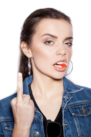 finger licking: Fashion girl biting gelatin candy and showing middle finger on white background not isolated