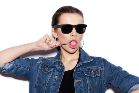isolated woman: Girl wearing blue jeans jacket licking candy. Young Woman in a sunglasses on white background not isolated Stock Photo