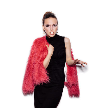 pink fur: Fashion Beauty Girl wearing black dress and pink fur coat showing spite. Gorgeous young Woman Portrait. Stylish Haircut and Makeup. Vogue style studio shot on white background not isolated Stock Photo