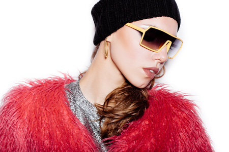 pink fur: Fashion sexy woman in sunglasses wearing silver dress, pink fur coat, black beanie hat.  White background, not isolated