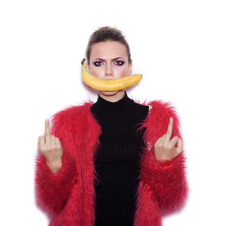 pink fur: Fashion swag female model wearing black dress and pink fur coat making fun with banana. Cute girl having fun over white background not isolated