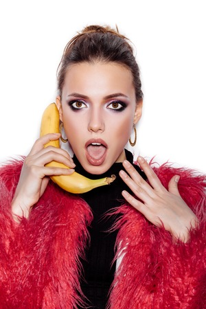 Fashion swag girl wearing black dress and pink fur coat making fun with banana. Woman holding a banana as a telephone over a white background not isolated