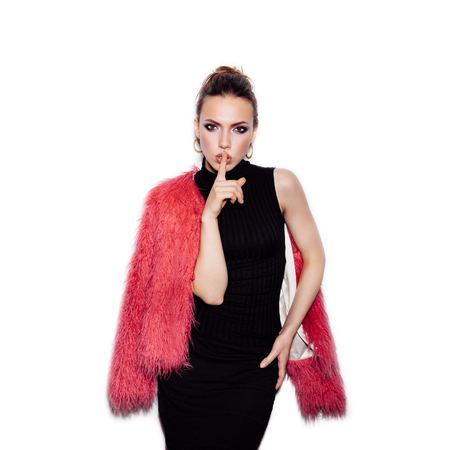 finger on lips: Fashion Beauty Girl wearing black dress and pink fur coat with finger on her lips showing to keep silence, hush. Gorgeous young woman. Vogue style studio shot on white background not isolated