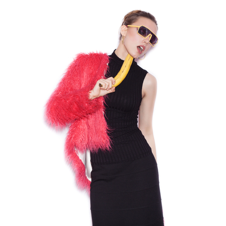 pink fur: Fashion swag woman wearing black dress and pink fur coat making fun with banana. Cute girl having fun over white background not isolated