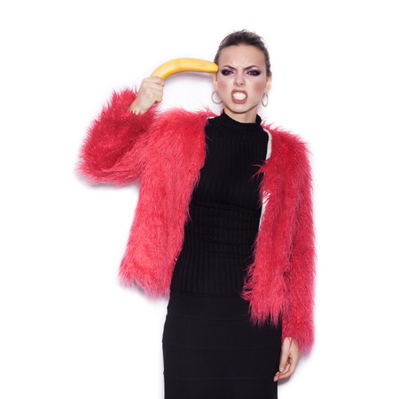 pink fur: Fashion sexy woman wearing black dress and pink fur coat making fun with banana. Cute girl having fun over white background not isolated