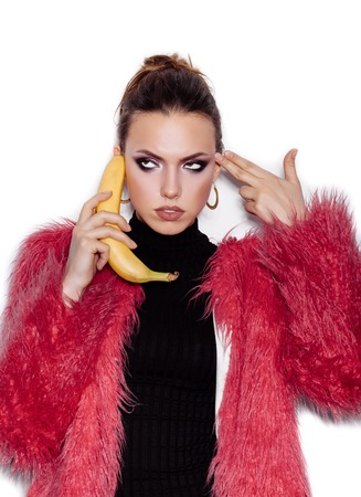 pink fur: Fashion swag girl wearing black dress and pink fur coat making fun with banana. Woman holding a banana as telephone and having fun over white background not isolated
