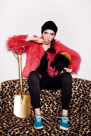 gold shovel: Fashion Beauty Girl wearing black dress and beanie and pink fur coat licking candy. Freak young Woman sitting on leopard sofa and holding gold helmet and shovel. Vogue style indoors shot