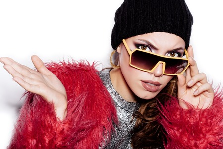 pink fur: Fashion female model in sunglasses wearing silver dress pink fur coat black beanie hat .  White background, not isolated