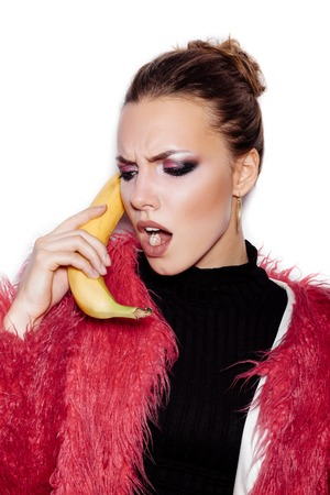 pink fur: Fashion swag female model wearing black dress and pink fur coat making fun with banana. Woman holding a banana as telephone and having fun over white background not isolated Stock Photo