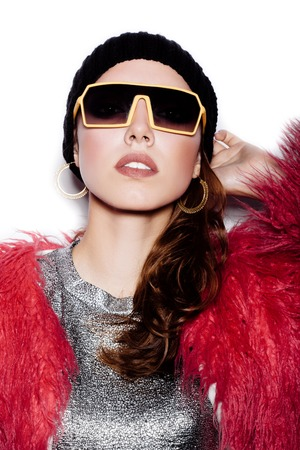 pink fur: Fashion girl hipster in sunglasses wearing silver dress, pink fur coat, black beanie hat.  White background, not isolated