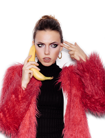 pink fur: Fashion swag sexy woman wearing black dress and pink fur coat making fun with banana. Woman holding a banana as telephone and having fun over white background not isolated Stock Photo
