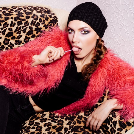 donna sexy: Moda malloppo Ragazza che porta vestito nero e berretto e cappotto di pelliccia rosa leccare caramelle. Freak giovane donna sexy sdraiata sul divano leopardo. Stile di moda ha sparato in casa
