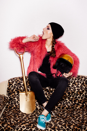 Fashion female model wearing black dress and beanie and pink fur coat licking candy. Freak young Woman sitting on leopard sofa and holding gold helmet and shovel. Vogue style indoors shot