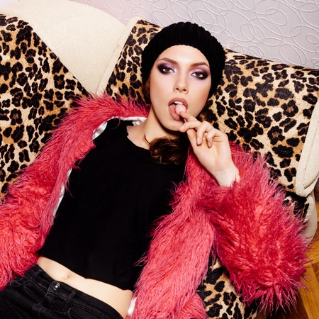 beanie: Fashion swag female model wearing black dress and beanie and pink fur coat licking candy. Freak young sexy Woman lying on leopard sofa. Vogue style indoors shot Stock Photo
