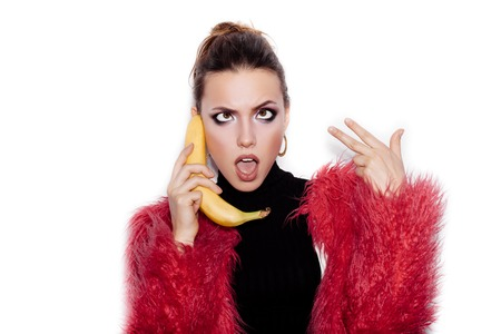 Fashion swag female model wearing black dress and pink fur coat making fun with banana. Woman holding a banana as a telephone over a white background not isolated photo