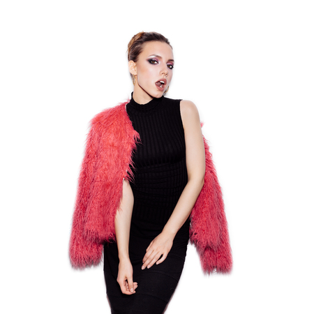 Fashion Beauty female model wearing black dress and pink fur coat. Gorgeous young Woman Portrait. Stylish Haircut and Makeup. Vogue style studio shot on white background not isolated Stockfoto