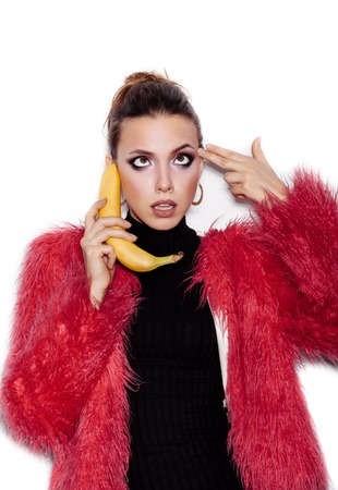 Fashion swag woman wearing black dress and pink fur coat making fun with banana. Woman holding a banana as a telephone and having fun over a white background not isolated photo