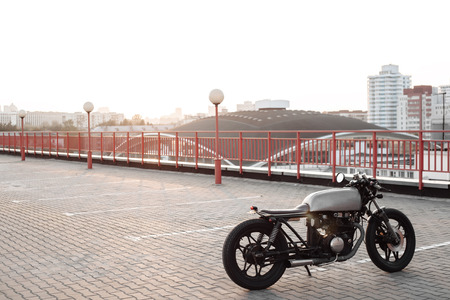 a lot  of: Vintage custom caferacer motorcycle in the parking lot during sunset. Outdoors lifestyle