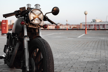 a lot  of: Vintage custom caferacer motorcycle in the parking lot during sunset. Stylish motorbike.  Outdoors lifestyle