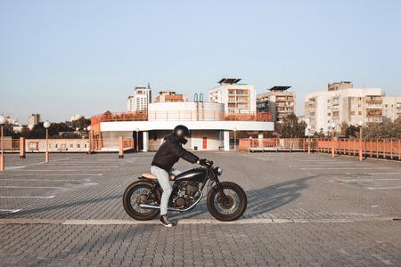 casco moto: Motorista que se sienta en una bicicleta en el estacionamiento en la ciudad con el cielo abierto en el fondo. Moto personalizada Vintage Foto de archivo
