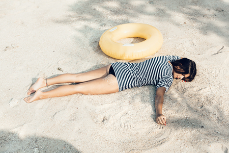 girl lying: Young female model lying on the beach, sunbathing and relaxing. Summer journey to the tropical island Stock Photo
