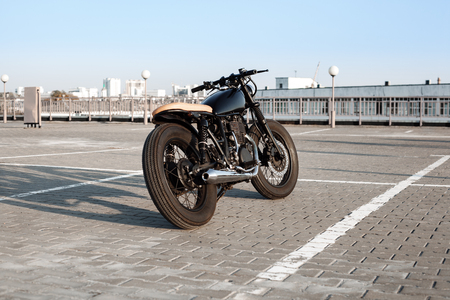 a motorcycle: Vintage custom motorcycle in the parking lot during sunset. Road and city with open sky on background. Stock Photo