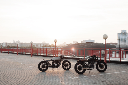 old motorcycle: Two vintage custom motorcycles in the parking lot during sunset
