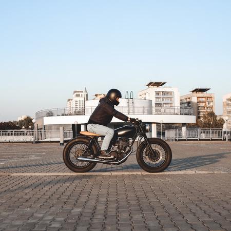 motociclista: Paseos a Motorista en una motocicleta en la playa de estacionamiento en la ciudad con el cielo abierto en el fondo. Moto personalizada Vintage Foto de archivo