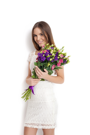female beauty: Young cute woman holding a bunch of flowers while standing against white background not isolated