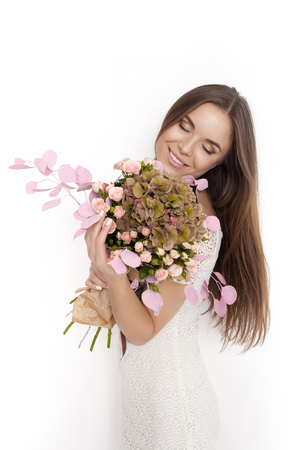 sexy birthday: Happy surprised model woman smelling flowers while standing against white background not isolated Stock Photo