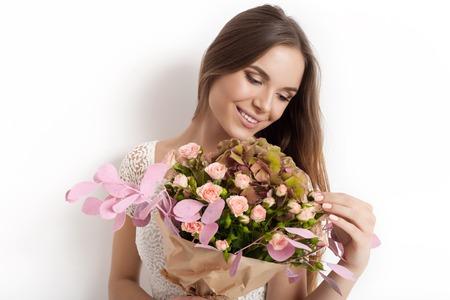 春の花の花束を持つ女性。ハッピー驚くモデル女性の花の臭いがします。母の日。春