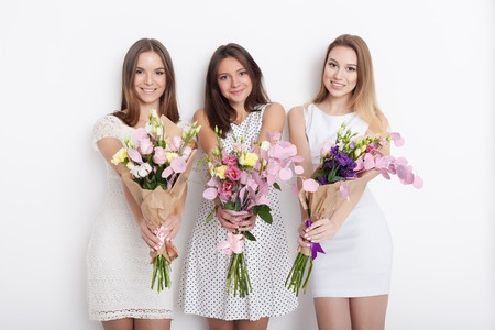 Three young cute women holding a bunch of flowers while standing against white background not isolated