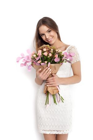 mujer con rosas: mujer linda joven que sostiene un ramo de flores mientras está de pie contra el fondo blanco no aislados