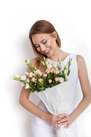 adult birthday: Happy surprised model woman smelling flowers while standing against white background not isolated Stock Photo