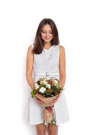voluptuous: D�a de San Valent�n - Sue�o voluptuosa mujer joven con el ramo de flores mientras est� de pie contra el fondo blanco no aislados. Serie de fotos