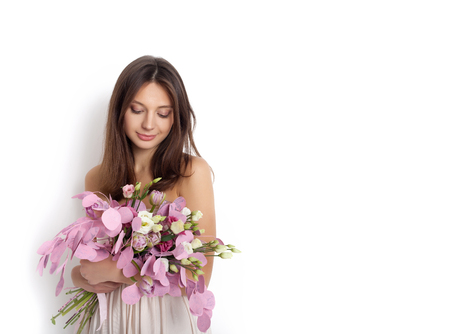 white woman: Happy surprised model woman smelling flowers while standing against white background not isolated Stock Photo
