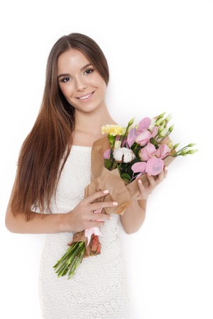 voluptuous: Valentines Day - Dreaming Voluptuous Young Woman with Bouquet of Flowers while standing against white background not isolated. Series of photos Stock Photo