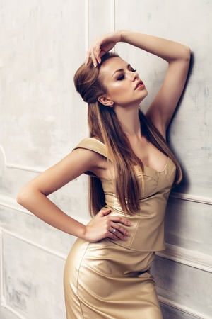 woman hairstyle: Fashion portrait of young sexy woman with hairstyle wearing golden dress Stock Photo