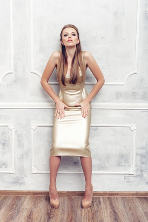 posing: Fashion portrait of young sexy woman with hairstyle wearing golden dress Stock Photo