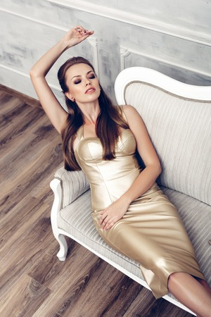 sexy dress: Fashion portrait of young sexy woman with hairstyle wearing golden dress Stock Photo