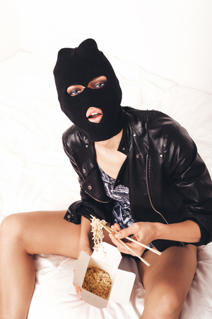 Girl wearing balaclava sitting on bed and eating noodle Stock Photo