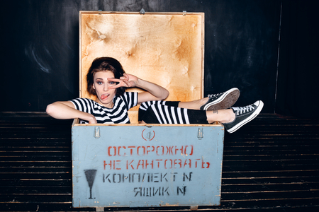 outcast: Girl wearing striped pajamas sitting in wooden box