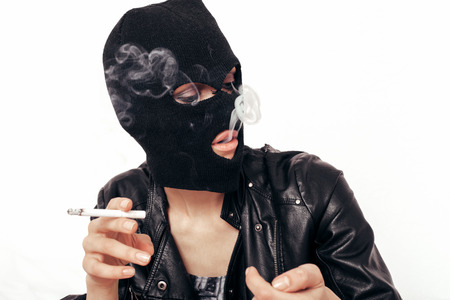Young female model in balaclava smoking cigarette