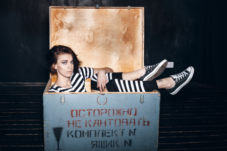 office slave: Girl wearing striped pajamas sitting in wooden box