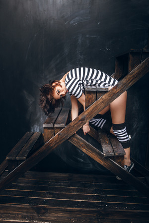 striped pajamas: Girl in a striped bodysuit against the black wall, lifestyle portrait of funny woman, caucasian model
